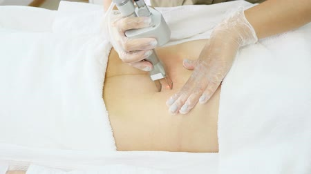 professional beauty clinic worker makes laser hair removal on patient belly with special equipment extreme close view