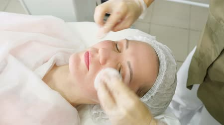 beauty salon therapist in white sterile gloves rinses patient face after laser hair removal close view Stock Footage