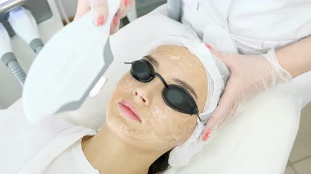 young woman patient in special black glasses lies on white couch and beauty salon therapist makes laser epilation closeup