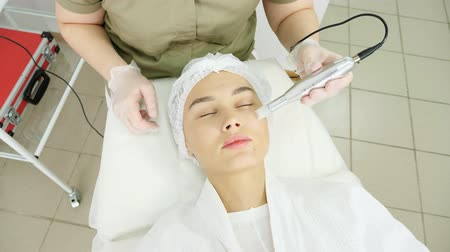 therapist in sterile gloves moves microdermabrasion device on medical beauty clinic woman visitor face close upper view