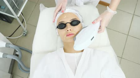 young woman patient in special black glasses lies on white couch and beauty salon therapist makes laser epilation top view