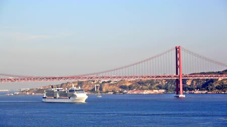 lisboa : big ship floats under the bridge on April 25 in Lisbon, Portugal Vídeos