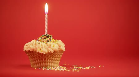 queque : Cupcake with the burning festive candle on a red background Vídeos