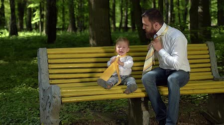 günler : Dad and son are sitting on a yellow bench in the park and putting on ties. Fathers Day. Stok Video