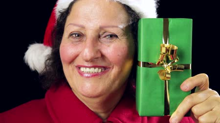 imitação : Close-up of an elderly lady in red Santa Claus outfit. She is brimming over with a smile, while raising, showing, and pointing at a green wrapped present. Tightly framed head shot. Black background.