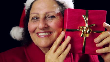 imitação : Close-up of a smiling female senior in red coat wearing a Santa Claus cap. She is raising, caressing and pointing at a wrapped, red Christmas present. Tightly framed head shot on black background.