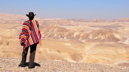 álmodozó : A man in a hat and a poncho looks around in the desert.