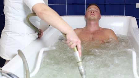 banheira : The young man is the procedure in the whirlpool hydrobath Stock Footage