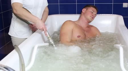 джакузи : The young man is the procedure in the whirlpool hydrobath Стоковые видеозаписи
