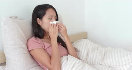 coughing : Woman getting sick and sneezing on bed Stock Footage
