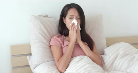 nariz : Woman feeling sick and sneezing on bed