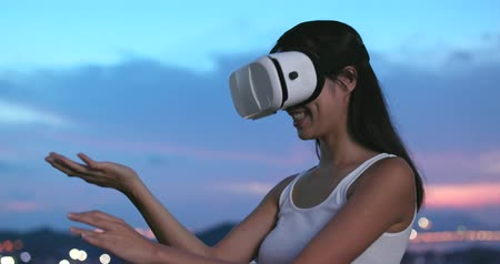 будущее : Woman watching on virtual reality device at sunset time