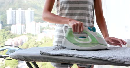 гладильный : Woman ironing clothes at home