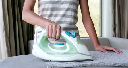 housekeeper : Woman ironing clothes at home
