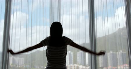 dobranoc : Woman stretching hand and open the curtain at home