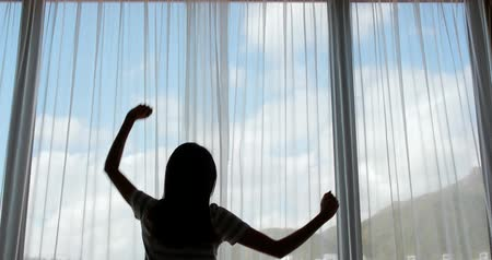 gritar : Young woman opening her bedroom curtains in the morning