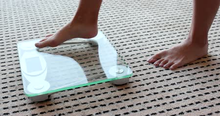 com escamas : Female measuring weight on health scale