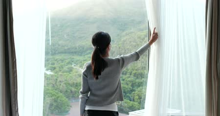 unveil : Woman unveil the window curtain at home