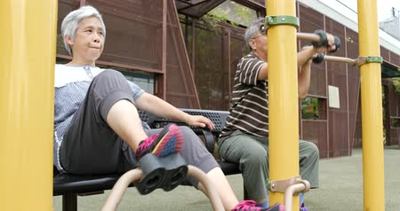 ciclismo : Senior couple doing exercise at outdoor park Stock Footage