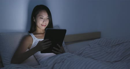 чтение : Woman use of tablet on bed Стоковые видеозаписи