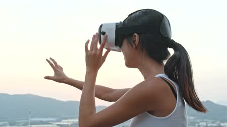 mobile game : Woman playing with virtual reality device on roof top building