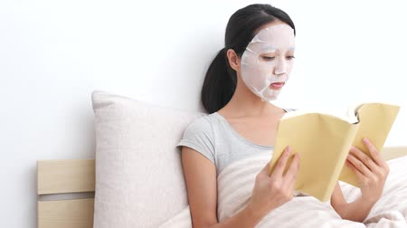coffee house : Woman use of paper mask on face and read book on bed Stock Footage