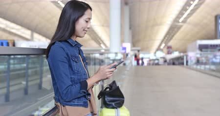menetrend : Woman use of mobile phone in Hong Kong airport