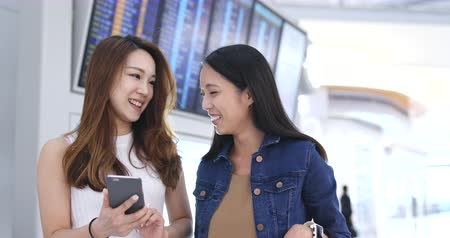 menetrend : Girl friends checking time schedule on cellphone in airport