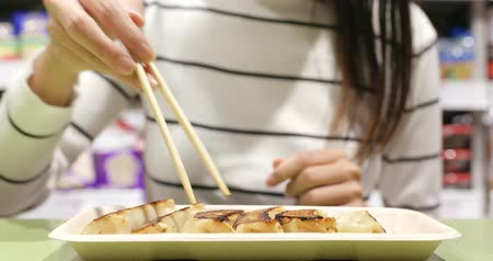 bamboo steamer : Woman eating meat dumpling in restaurant