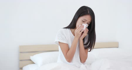 alergia : Woman sneezing on bed Wideo