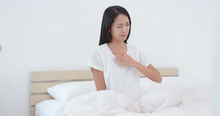 wheeze : Woman feeling back pain and tired on bed Stock Footage
