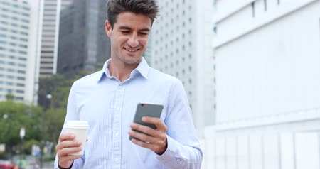 spaniard : Hispanic man using cellphone with his coffee