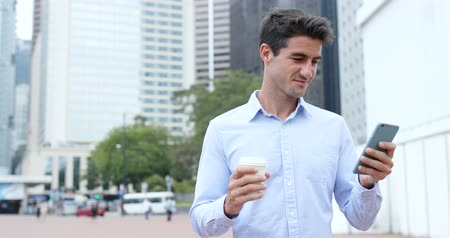 spaniard : Hispanic man looking at cellphone with his coffee Stock Footage