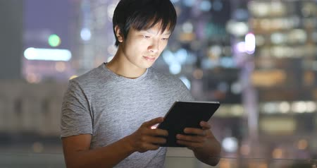 um : Asian young man use of tablet computer at night