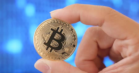 háló : Holding bitcoin over blue background
