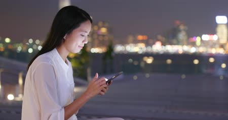 Young Asian Woman text cellphone at night