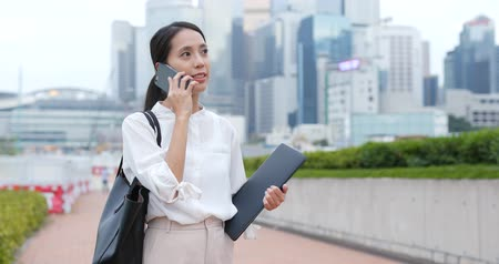 um : Businesswoman talk to mobile phone and hold with laptop computer