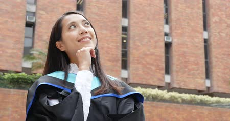 mortarboard : Woman wearing graduation gown and think of future