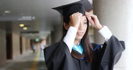 grãos : Woman graduation and wearing graduation gown