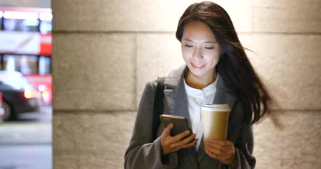Asian businesswoman use of mobile phone and hold with hot coffee