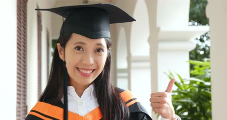 akademický : Woman wear graduation gown and showing thumb up