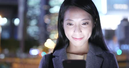 tilt shift : Businesswoman use of mobile phone in city at night Stock Footage