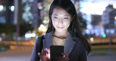 tilt shift : Asian Woman use of smart phone in city at night Stock Footage