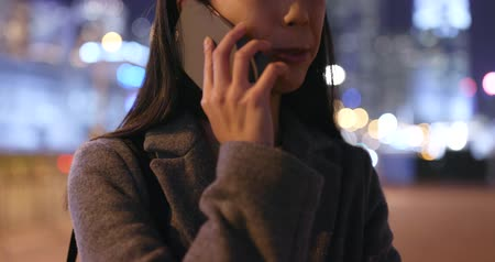 Woman talk to mobile phone in city at night