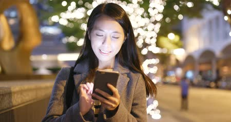 tilt shift : Woman sending sms on cellphone at night Stock Footage