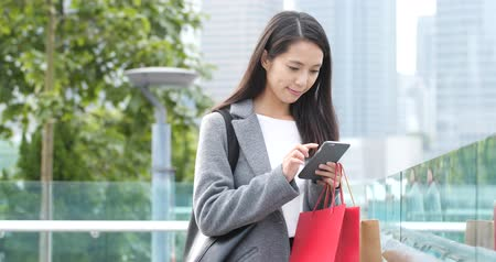 tilt shift : Young woman using mobile phone and holding shopping bag Stock Footage