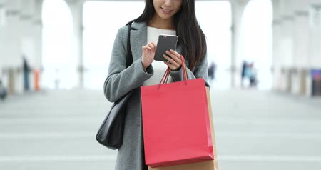 tilt shift : Woman use of smart phone and holding shopping bag