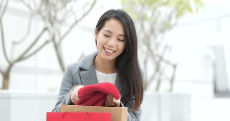 Woman picking out from paper bag after shopping