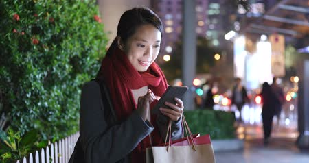sacchetto carta : Woman use of smart phone in city at night and hold with shopping bag Filmati Stock