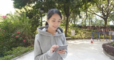 ler : Woman walking in park and use of mobile phone